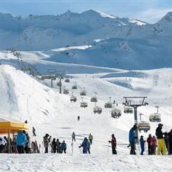 Skifahrer auf Skipiste mit Sessellift im Hintergrund