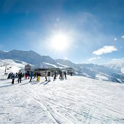 Skifahrer in einem Skigebiet bei strahlendem Sonnenschein