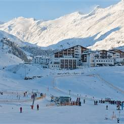 Exterior view of hotels in front of a mountain landscape in winter
