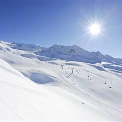 Skigebiet vor Berglandschaft bei strahlendem Sonnenschein