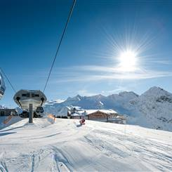 Ski area with gondolas and ski hut in bright sunshine