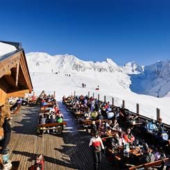 Aprés Ski Skihütte an Skipiste vor Berglandschaft