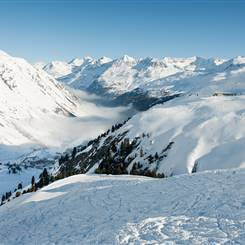 Ski slopes in front of snow-covered mountains