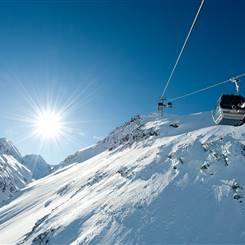 Gondel vor Berglandschaft im Winter bei strahlendem Sonnenschein