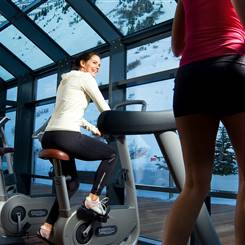 Woman on ergometer in front of panorama front with view of mountains