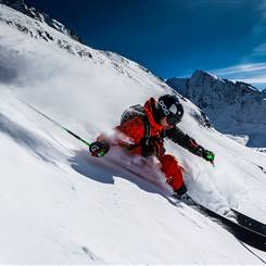 Freerider in deep snow in front of a mountain landscape