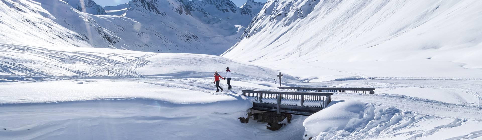 Couple hikes in winter landscape towards Schönwies hut