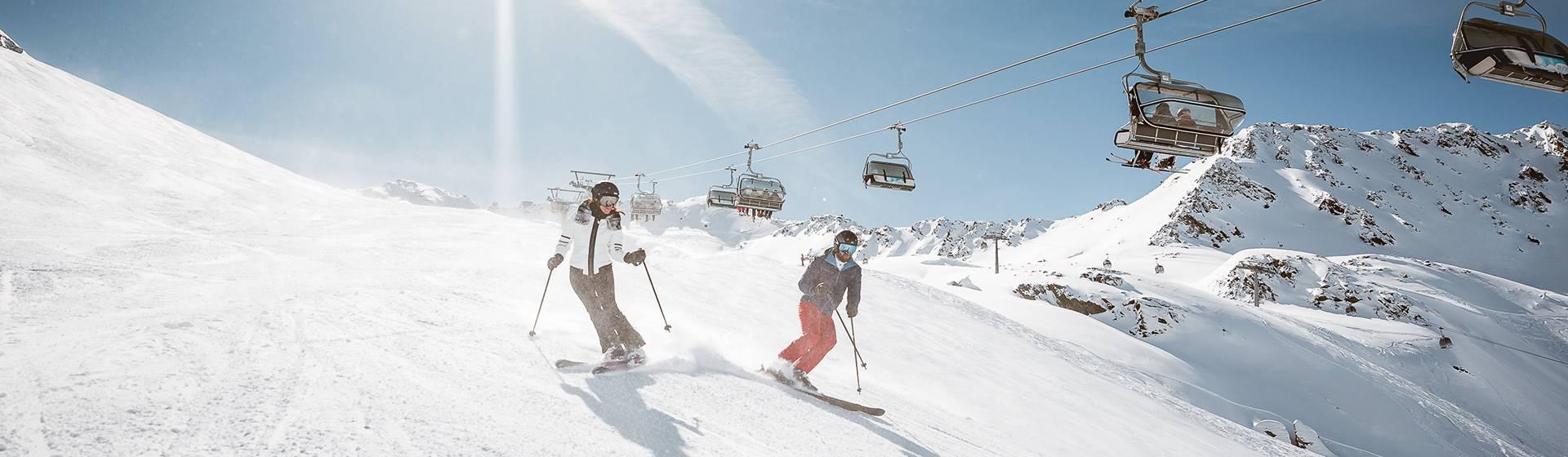 Zwei Skifahrer auf Skipiste unter Sessellift