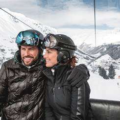 Couple in ski outfit and helmet in a gondola