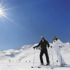 Paar in Skioutfit auf Skipiste bei strahlendem Sonnenschein