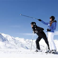 Couple in ski outfit on ski slope in sunshine